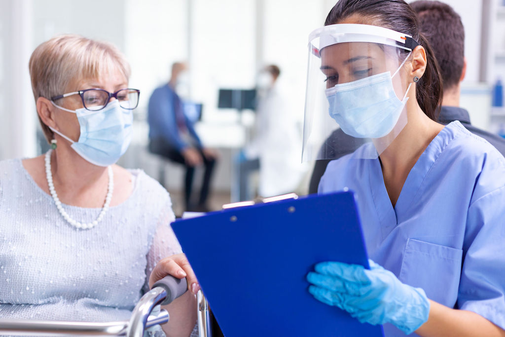 Medical staff wearing visor against coronavirus in hospital hallway talking disabled senior woman wearing face mask. Patient and medical staff in waiting area. Doctor in examination room.